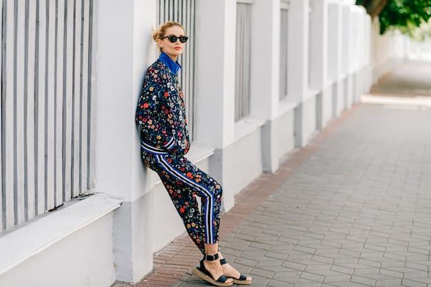 Mooie stijlvolle blonde model in gekleurd pak poseren in de straat