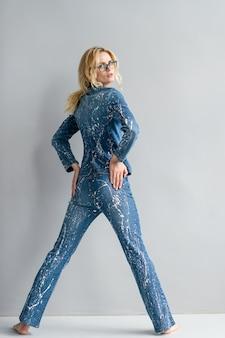Mooie stijlvolle blonde model in jeans pak poseren