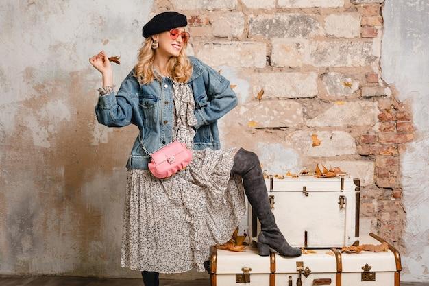 Mooie stijlvolle blonde vrouw in spijkerbroek en oversized jas poseren tegen muur in straat