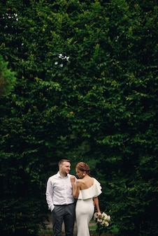 Mooie stijlvolle bruid en bruidegom op de wandeling in het park op hun trouwdag