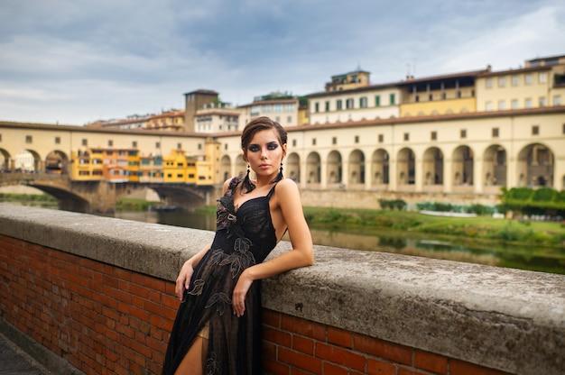 Mooie stijlvolle bruid in een zwarte jurk staat aan de kade in florence, italië.