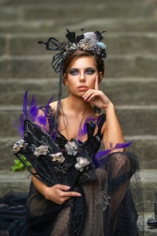 Mooie stijlvolle bruid in een zwarte jurk zit op de trap in florence, italië.