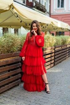 Mooie stijlvolle brunette vrouw poseren in rode jurk op stadsoppervlak