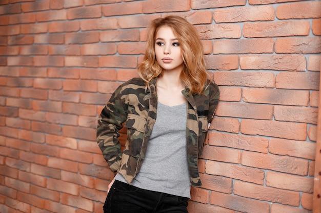 Mooie stijlvolle charmante sexy jonge vrouw in een stijlvolle militaire camouflage jas in een grijs t-shirt en stijlvolle zwarte spijkerbroek staan in de studio in de buurt van de bakstenen muur. moderne mode schattig meisje