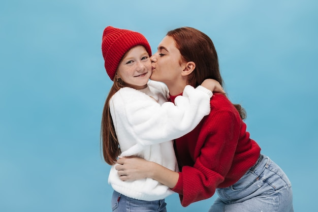 Mooie stijlvolle dame in rode heldere trui en spijkerrok zoenen op wang jong gembermeisje in wollen hoed en witte oversized trui op blauwe muur