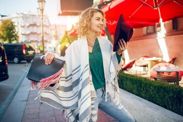 Mooie stijlvolle dame wandelen in de straat in cape met handtas, mode-accessoires, lente streetstyle trend, glimlachend