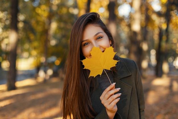 Mooie stijlvolle gelukkig meisje met een glimlach in een modieuze jas met een gouden herfstblad in de buurt van het gezicht tijdens het wandelen in het park. leuke vrouwen.