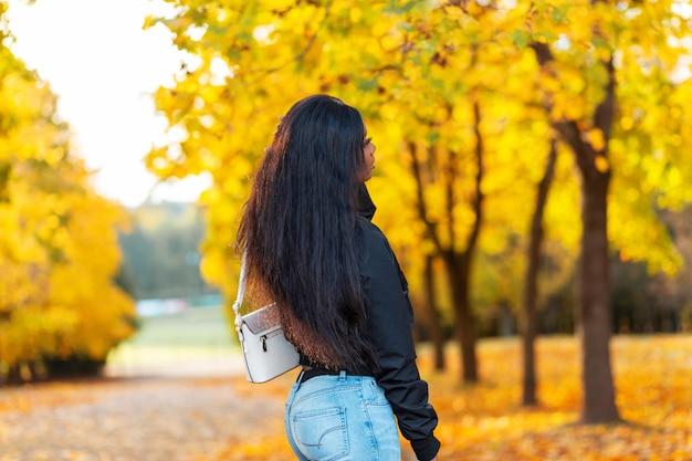 Mooie stijlvolle jonge afrikaanse vrouw model met lang haar in een mode zwarte jas met jeans en een tas loopt in een herfstpark met fel geel herfstgebladerte. vrouwelijke casual stijl en schoonheid