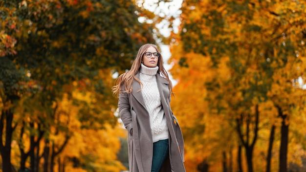 Mooie stijlvolle jonge hipster vrouw in een modieuze gebreide trui in een elegante lange jas in spijkerbroek met bril loopt door een herfstpark tussen bomen met oranje gebladerte. mooi meisje buitenshuis.