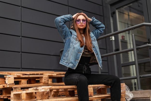Mooie stijlvolle jonge hipster vrouw in paarse trendy bril in blauwe stijlvolle denim jasje in zwarte vintage jeans poseren op houten pallets in de stad. mooi meisje mannequin buitenshuis. straatstijl