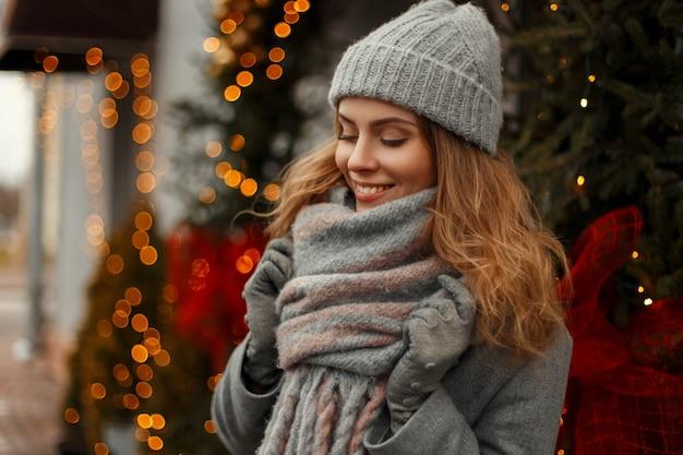 Mooie stijlvolle jonge vrouw die lacht in gebreide modieuze kleding met een muts en sjaal op een vakantie in de buurt van de lichten en een kerstboom op een besneeuwde dag