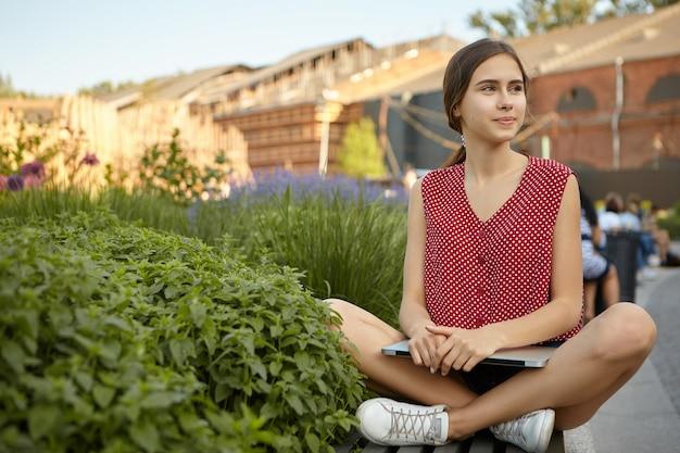 Mooie stijlvolle jonge vrouw freelancer dragen witte sneakers en rode polka top zittend op een bankje benen gekruist houden, laptop vasthouden, met behulp van gratis wifi in stadspark voor verre werk op afstand