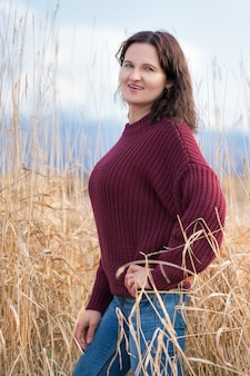 Mooie stijlvolle jonge vrouw gekleed in bruine trui, spijkerbroek permanent en poseren in gedroogd gras in veld in de herfst. mooie vrouw met lang krullend donkerbruin haar en rode lippen.