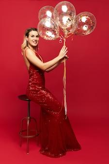 Mooie stijlvolle jonge vrouw, gekleed in lage nek rode jurk poseren en houden ballonnen