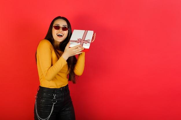 Mooie stijlvolle jonge vrouw in een gele blouse en rode bril houdt een geschenkdoos over rood oppervlak