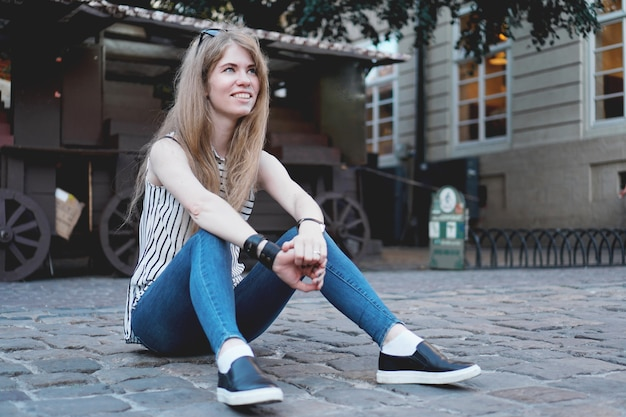 Mooie stijlvolle jonge vrouw in gestreepte blouse zittend op de geplaveide weg van de stad