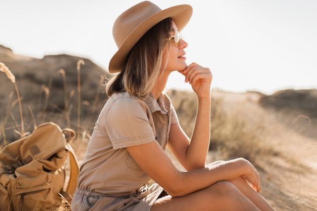 Mooie stijlvolle jonge vrouw in kaki jurk in woestijnzand reizen in afrika op safari hoed en rugzak dragen