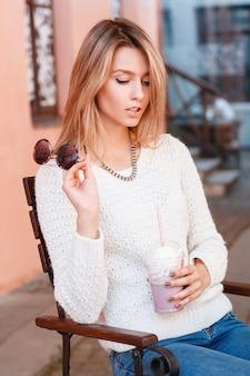 Mooie stijlvolle jonge vrouw in vintage gebreide trui in stijlvolle spijkerbroek zit op een houten stoel op een terras met een plastic beker in haar handen. mooi meisje dat en een cocktail rust drinkt.