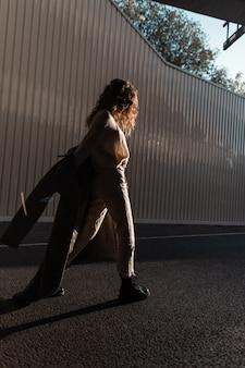 Mooie stijlvolle jonge vrouw met krullend haar in de mode lange jas loopt in de stad in zonlicht en schaduwen. stedelijke casual stijl