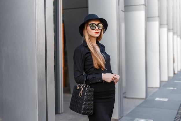 Mooie stijlvolle jonge zakenvrouw in een hoed en zonnebril met een handtas