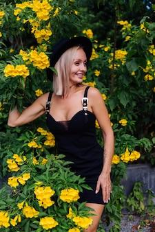 Mooie stijlvolle kaukasische gelukkige vrouw in zwarte jurk en klassieke hoed in park omgeven door gele thaise bloemen