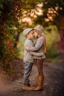 Mooie stijlvolle kinderen broer en zus in de herfst op een wandeling in het park
