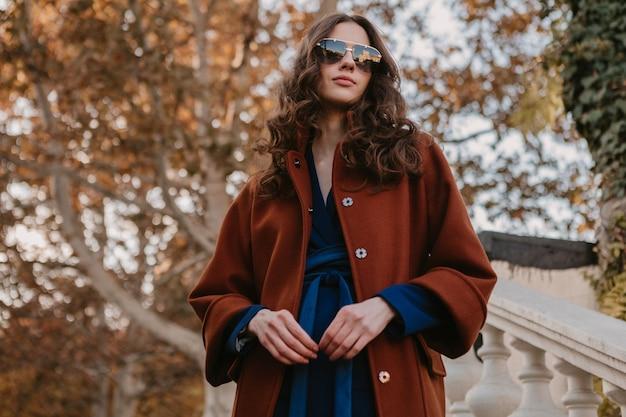 Mooie stijlvolle lachende magere vrouw met krullend haar lopen in straat trappen gekleed in warme bruine jas en blauw pak, herfst trendy mode streetstyle