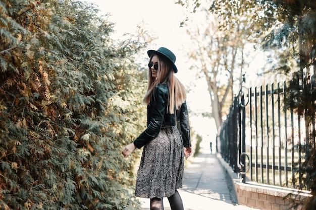 Mooie stijlvolle lachende vrouw in mode outfit look met leren jas en vintage jurk loopt buiten