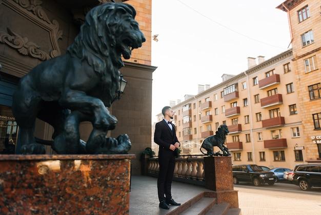 Mooie stijlvolle man bruidegom wachten op zijn bruid in de stad van europa. bruiloft concept