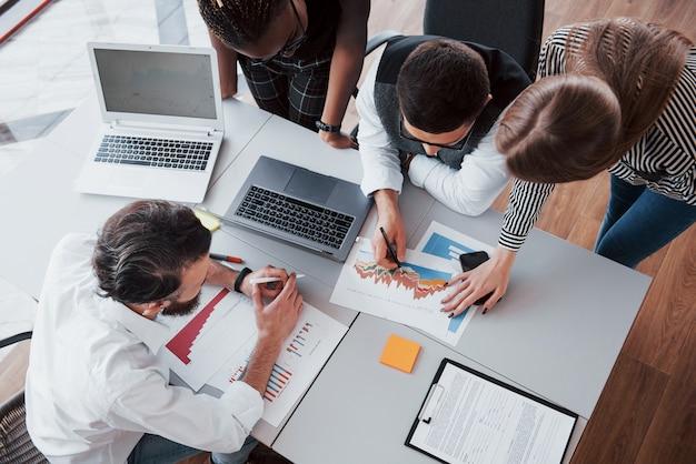 Mooie stijlvolle medewerkers zitten in het kantoor aan de balie met behulp van een laptop en luisteren naar een collega.