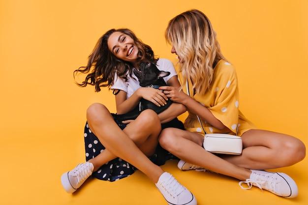 Mooie stijlvolle meisjes zitten met gekruiste benen op de grond en spelen met hond. mooie europese zusters poseren op geel met zwarte bulldog pup.