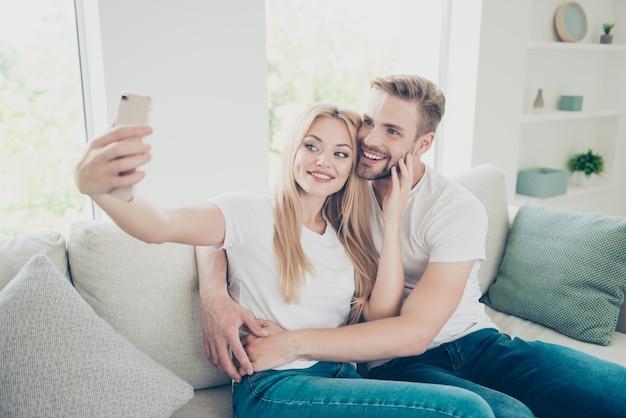 Mooie stijlvolle paar in casual t-shirts en spijkerbroek thuis selfie maken