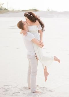 Mooie stijlvolle paar poseren op het strand