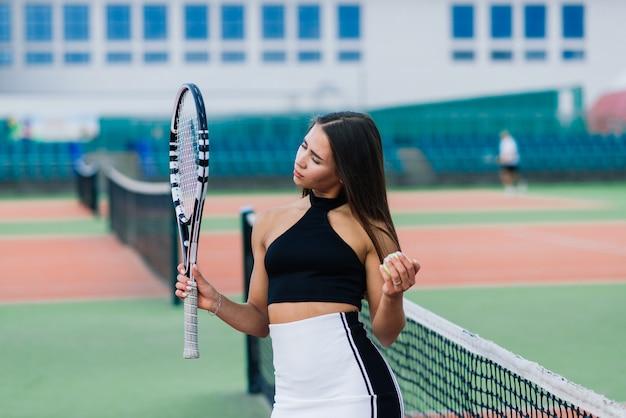 Mooie stijlvolle sexy vrouw in een trendy sportkleding op de tennisbaan.