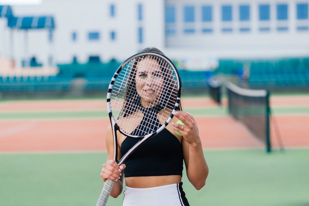 Mooie stijlvolle sexy vrouw in een zwarte trendy sportkleding op tennisbaan.