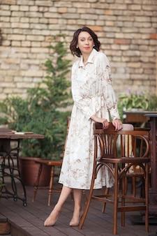 Mooie stijlvolle vrouw in beige jurk in café buiten. portret van gelukkig wijfje in openluchtkoffie