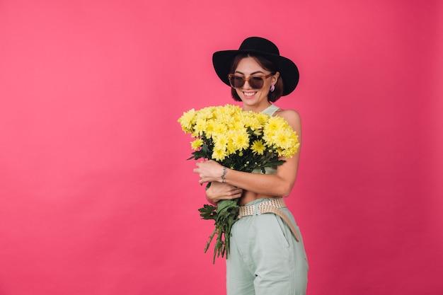 Mooie stijlvolle vrouw in hoed en zonnebril poseren, met groot boeket gele asters, lentestemming, positieve emoties geïsoleerde ruimte