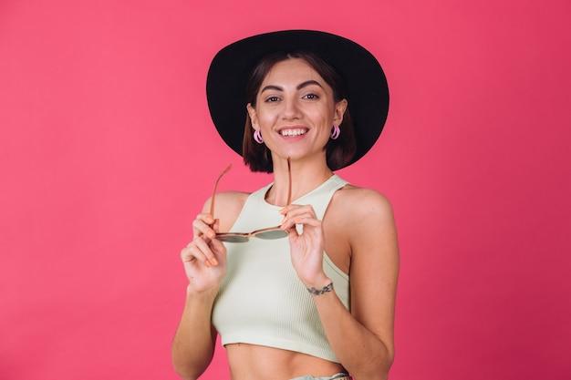 Mooie stijlvolle vrouw in hoed en zonnebril poseren over roze rode muur