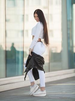 Mooie stijlvolle vrouw in modieuze kleding met witte schoenen staat in de buurt van een moderne muur