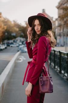 Mooie stijlvolle vrouw in paars pak wandelen in de stad straat, lente zomer herfst seizoen modetrend dragen hoed, portemonnee te houden