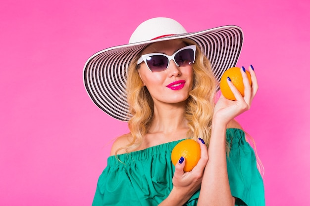 Mooie stijlvolle vrouw in zonnebril en hoed met sinaasappels