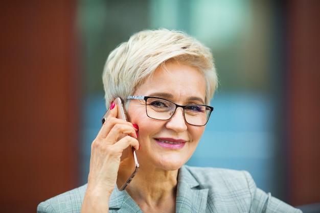 Mooie stijlvolle vrouw met een kort kapsel in een pak roept aan de telefoon
