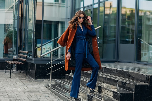 Mooie stijlvolle vrouw met wandelen in de zakelijke straat van de stedelijke stad gekleed in warme bruine jas en blauw pak, lente herfst trendy mode streetstyle, zonnebril dragen