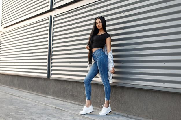 Mooie stijlvolle vrouw met zonnebril in modieuze kleding met witte schoenen