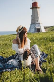 Mooie stijlvolle vrouw op het platteland, met een hond