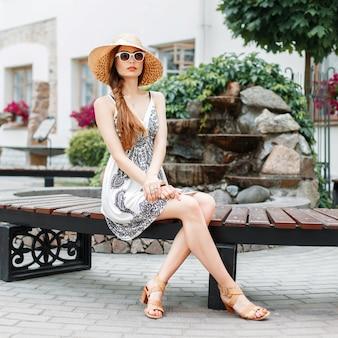 Mooie stijlvolle vrouw rusten op een bankje.