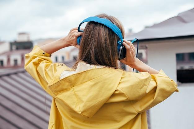 Mooie stijlvolle vrouw zijn luisteren muziek en poseren buiten, veel plezier en voelt zich vrij met een glimlach