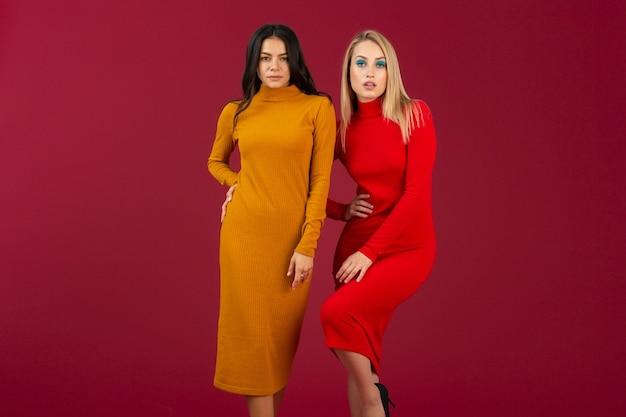 Mooie stijlvolle vrouwen in gele en rode herfst winter mode gebreide jurk poseren geïsoleerd op rode muur