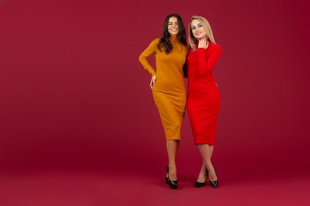 Mooie stijlvolle vrouwen vrienden in gele en rode herfst winter mode gebreide jurk poseren geïsoleerd op rode muur