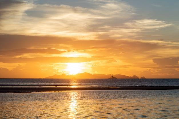 Mooie strandzonsondergang met blauwe overzees en gouden lichte hemelwolk